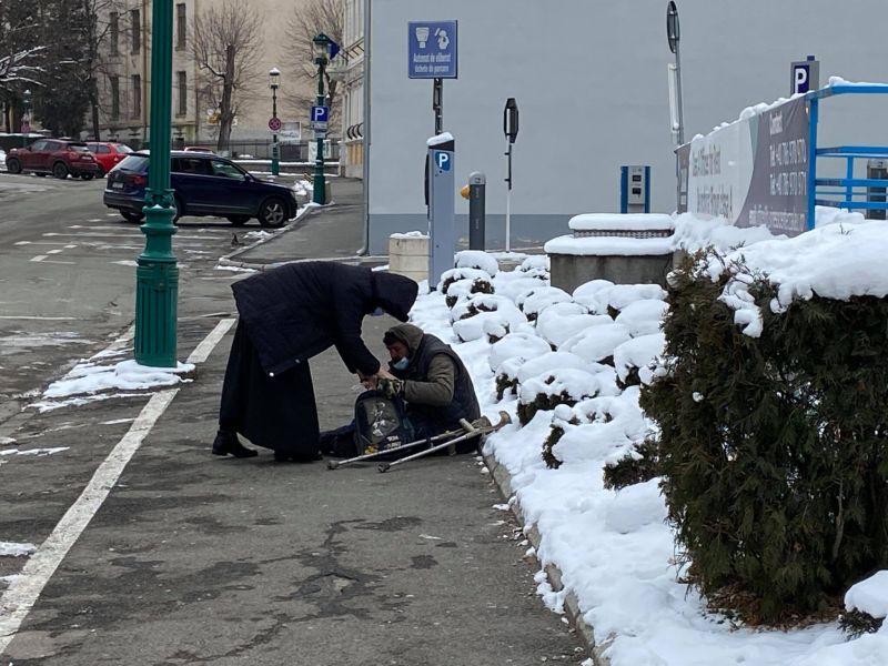 O călugăriță ajută un om al străzii căzut în zăpadă în centrul Zalăului